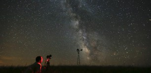 FILE - In this Wednesday, July 23, 2014 file photo, Omaha photographer Lane Hickenbottom photographs the night sky in a pasture near Callaway, Neb. With no moon in the sky, the Milky Way was visible to the naked eye. More than one-third of the world's population can no longer see the Milky Way because of man-made lights, according to a scientific paper by Light Pollution Science and Technology Institute's Fabio Falchi and his team members, published on Friday, June 10, 2016. (Travis Heying/The Wichita Eagle via AP) LOCAL TELEVISION OUT; MAGS OUT; LOCAL RADIO OUT; LOCAL INTERNET OUT; MANDATORY CREDIT