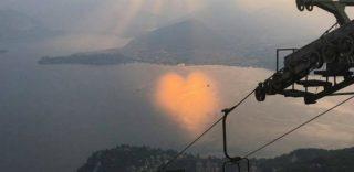Sul lago Maggiore il sole proietta un cuore di luce: la fotografia del tramonto è irripetibile