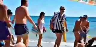 """""""Rigore per la Juve!"""": i bagnanti cadono a terra intorno al tifoso che cammina sulla spiaggia"""