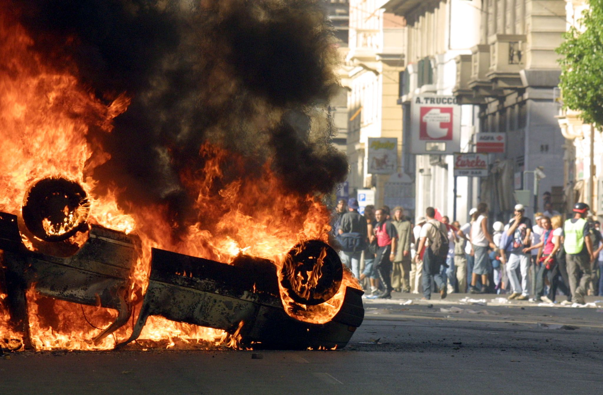 A car burns after anti-globalisation activists clashed with the police during a protest against the G8 summit in Genoa 21July 2001. Italian police and protestors clashed Saturday on the second day of protests in the Mediterranean city hosting the Group of Eight (G8) summit. Police repeatedly fired tear gas at groups of protestors who broke away from a crowd of some 50,000 demonstrators, most of whom filed peacefully through the streets of the ancient port city. AFP PHOTO GERARD JULIEN (Photo credit should read GERARD JULIEN/AFP/Getty Images)