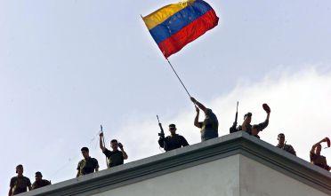 Soldati della Guardia nazionale venezuelana sventolano la bandiera   dal tetto del palazzo presidenziale Miraflores il 13 aprile 2002.  Foto di: JUAN BARRETO/AFP/Getty Images