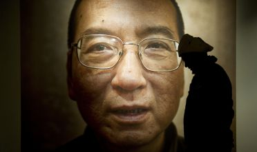 A man walks in front of a poster of Chinese dissident and peace prize laureate Liu Xiaobo at an exhibition at the Nobel Peace Center in Oslo, December 9, 2010. With the guest of honour stuck in a Chinese prison, this year's Nobel Peace Prize ceremony will centre around an empty chair, as its celebration of dissident Liu Xiaobo continues to split the global community and infuriate Beijing. The Norwegian Nobel Committee head said he was surprised at the level of international support for jailed Chinese dissident and peace prize laureate Liu Xiaobo despite pressure from Beijing.  AFP PHOTO/ODD ANDERSEN (Photo credit should read ODD ANDERSEN/AFP/Getty Images)