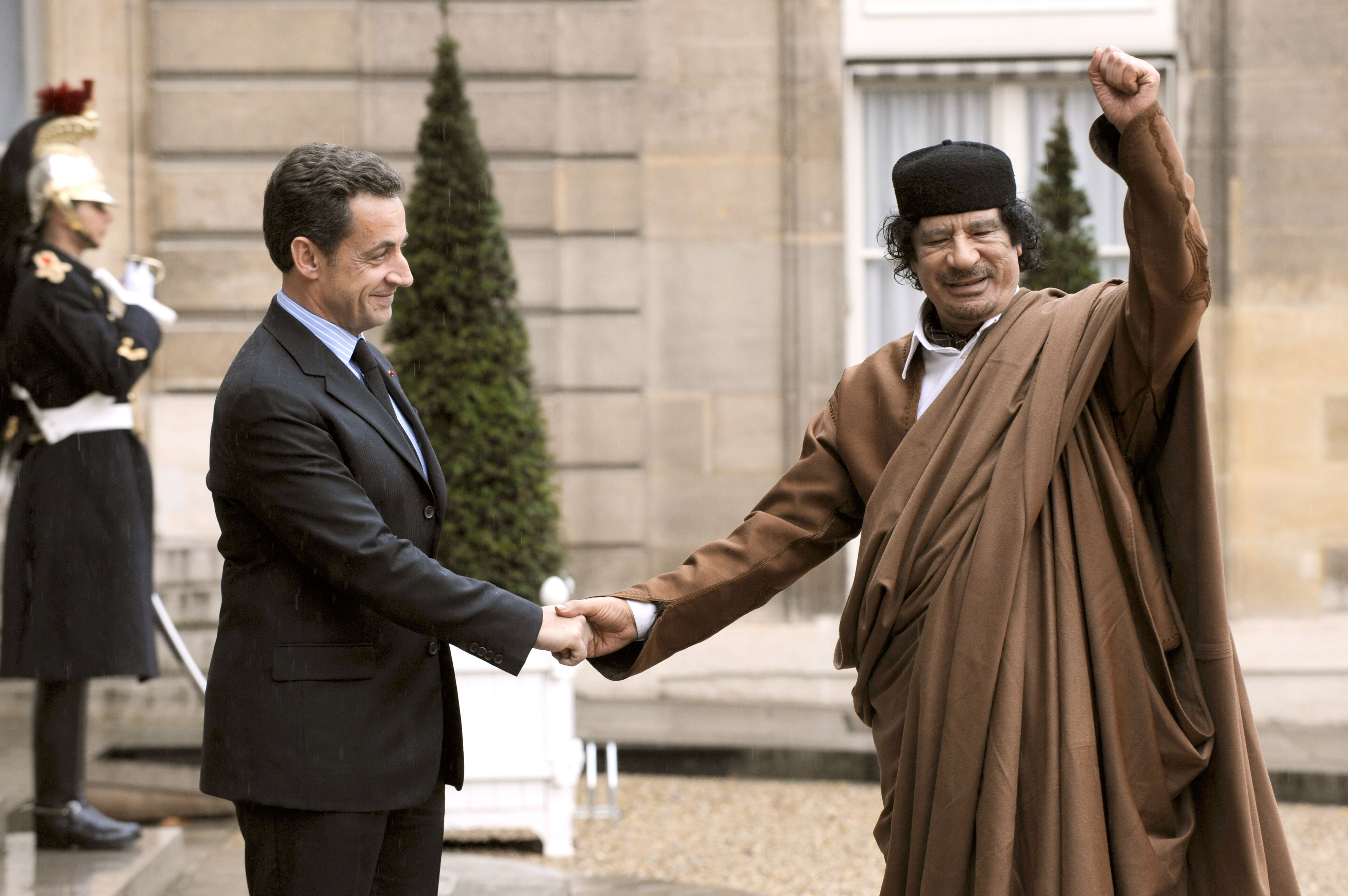 French president Nicolas Sarkozy (L) welcomes Libyan leader Moamer Kadhafi 10 December 2007 at the French Elysee Palace in Paris. A tent for Kadhafi has been erected in the gardens of the Hotel Marigny, the 19th-century mansion which is used as an official guesthouse for state visits. Kadhafi is on a five-day visit to France for a high-profile visit set to usher in multi-billion-euro nuclear and aviation contracts, even as critics lashed President Nicolas Sarkozy for inviting the former pariah. AFP PHOTO ERIC FEFERBERG (Photo credit should read ERIC FEFERBERG/AFP/Getty Images)