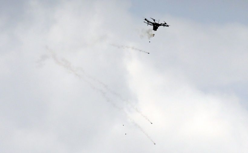 A picture taken on March 30, 2018 shows an Israeli border police drone dropping tear gas canisters during clashes with Palestinian protesters following demonstrations commemorating Land Day near the border with Israel, east of Gaza City. Land Day marks the killing of six Arab Israelis during 1976 demonstrations against Israeli confiscations of Arab land. / AFP PHOTO / MAHMUD HAMS / The erroneous mention[s] appearing in the metadata of this photo by MAHMUD HAMS has been modified in AFP systems in the following manner: [east of Gaza City] instead of [east of Jabalia]. Please immediately remove the erroneous mention[s] from all your online services and delete it (them) from your servers. If you have been authorized by AFP to distribute it (them) to third parties, please ensure that the same actions are carried out by them. Failure to promptly comply with these instructions will entail liability on your part for any continued or post notification usage. Therefore we thank you very much for all your attention and prompt action. We are sorry for the inconvenience this notification may cause and remain at your disposal for any further information you may require. (Photo credit should read MAHMUD HAMS/AFP/Getty Images)