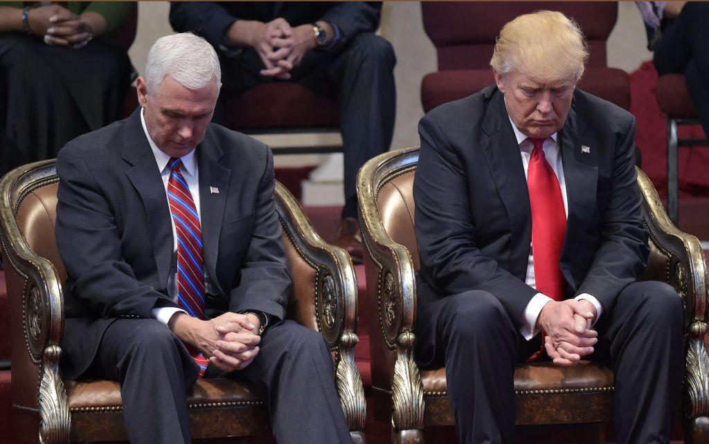 TOPSHOT - Republican presidential nominee Donald Trump (R) and running mate Mike Pence  bow their heads in prayer during the Midwest Vision and Values Pastors and Leadership Conference at the New Spirit Revival Center in Cleveland Heights, Ohio on September 21, 2016. / AFP PHOTO / MANDEL NGAN        (Photo credit should read MANDEL NGAN/AFP/Getty Images)