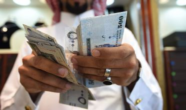 A man counts Saudi riyal banknotes at his jewelry shop in Tiba market in the capital Riyadh on October 3, 2016. / AFP / FAYEZ NURELDINE        (Photo credit should read FAYEZ NURELDINE/AFP/Getty Images)
