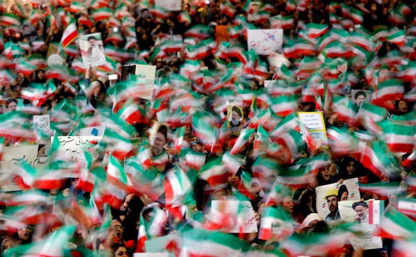 Supporters of Iranian presidential candidate Ebrahim Raisi wave national flags and raise his portrait as they attend a campaign rally at Imam Khomeini Mosque in the capital Tehran on May 16, 2017. Iran's presidential election on May 19 is effectively a choice between moderate incumbent Hassan Rouhani and hardline jurist Raisi, with major implications for everything from civil rights to relations with Washington. / AFP PHOTO / ATTA KENARE        (Photo credit should read ATTA KENARE/AFP/Getty Images)