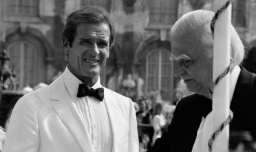 British actor Roger Moore (L) speaks with Willoughby Gray during the shooting of the James Bond film 'A View to a Kill' in Chantilly, just north of Paris on August 16, 1984, at the Chantilly Chateaux. British actor Roger Moore, who will forever be remembered for playing James Bond, died on May 23, 2017 aged 89, his family announced in a statement on Twitter. Moore was married four times and is survived by two sons and a daughter.  / AFP PHOTO / Pierre VERDY        (Photo credit should read PIERRE VERDY/AFP/Getty Images)