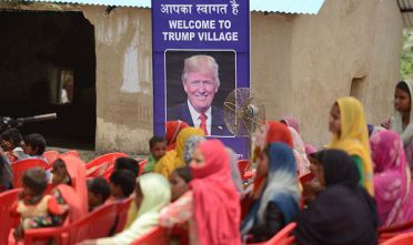 "Indian women gather to listen to a speaker next to a poster with the image of  US President Donald Trump during a ceremony at Marora village, which has been unofficially renamed 'Trump Village,"" about 100km from New Delhi, on June 23, 2017. A rural Indian settlement with little electricity or running water renamed itself ""Trump Village"" on June 23 in an unusual gesture to the American president ahead of Prime Minister Narendra Modi's trip to Washington. A huge billboard declaring ""Welcome to Trump Village"" in Hindi and English, accompanied with a beaming portrait of the US president, was unveiled in Haryana state's Marora, as the village is officially known. The water and sanitation group Sulabh, which has been installing toilets in the impoverished settlement, suggested the name change to the local council.  / AFP PHOTO / MONEY SHARMA        (Photo credit should read MONEY SHARMA/AFP/Getty Images)"