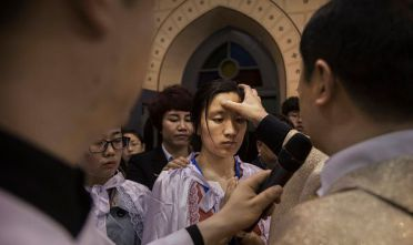 BEIJING, CHINA - APRIL 15: Chinese Catholic Bishop Zhang Hong, right, blesses newly baptized worshippers during a special ceremony at a mass on Holy Saturday during Easter celebrations at the government sanctioned West Beijing Catholic Church on April 15, 2017 in Beijing, China. China, an officially atheist country, places a number of restrictions on Christians, allowing legal practice of the faith only at state-approved churches. The policy has driven an increasing number of Christians and Christian converts 'underground' to congregations in private homes and other venues.  While the size of the religious community is difficult to measure, studies estimate there are more than 80 million Christians inside China; some studies support the possibility it could become the most Christian nation in the world in the coming years. Officially there have been no relations between China and the Vatican since the country's modern founding in 1949 though in recent years there have been signs of warming relations between Chinese president Xi Jinping and Pope Francis that could possibly allow greater religious freedom in the future. At present, the split means approved Chinese Christians worship within a state-sanctioned Church known as the Patriotic Association which regards the Communist Party as its leader, not the Pope in Rome. (Photo by Kevin Frayer/Getty Images)