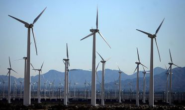 Palm Springs, UNITED STATES:  A windfarm is seen 30 December 2006 near Palm Springs, California. Increasingly popular as alternative sources of energy, wind turbine generators are a type of windmill that produces electricity by harnessing the wind. Wind turbine generators are much less harmful to the environment than burning fossil fuels, but they do require average wind speeds of at least 21 km/h (13 mph). The largest of these windmills stands 150 feet tall with blades half the legend of a football field. The compartments at the top containing the generator, hub and gearbox weigh 30,000 to 45,000 pounds. A wind turbine's cost can range upwards to USD 300,000 and can produce 300 kilowatts an hour -- the amount of electricity used by a typical household in a month. Almost all of the currently installed wind electric generation capacity is in California. The high-tech megatowers are engineered in cooperation with NASA and nursed by federal and state subsidies. This wind farm on the San Gorgonio Mountain Pass in the San Bernadino Mountains contains more than 4,000 separate windmills and provides enough electricity to power Palm Springs and the entire Coachella Valley. AFP PHOTO/GABRIEL BOUYS  (Photo credit should read GABRIEL BOUYS/AFP/Getty Images)