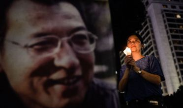 "A woman holds a candle as she attends a vigil for terminally-ill Nobel laureate Liu Xiaobo (pictured on banner) in Hong Kong on June 29, 2017. Liu wants Chinese authorities to let him get treatment abroad, friends say, as officials said his cancer has spread throughout his body. The Nobel Peace Prize winner, who was sentenced to 11 years in prison in 2009 for ""subversion"" after calling for democratic reforms, was released on medical parole after being diagnosed with terminal liver cancer last month, his lawyer said this week.  / AFP PHOTO / Anthony WALLACE        (Photo credit should read ANTHONY WALLACE/AFP/Getty Images)"