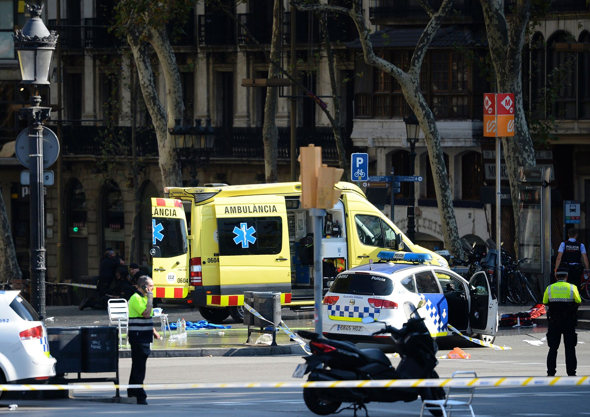 A policemen and a medical staff member stand past police cars and an ambulance in a cordoned off area after a van ploughed into the crowd, injuring several persons on the Rambla in Barcelona on August 17, 2017. / AFP PHOTO / Josep LAGO        (Photo credit should read JOSEP LAGO/AFP/Getty Images)