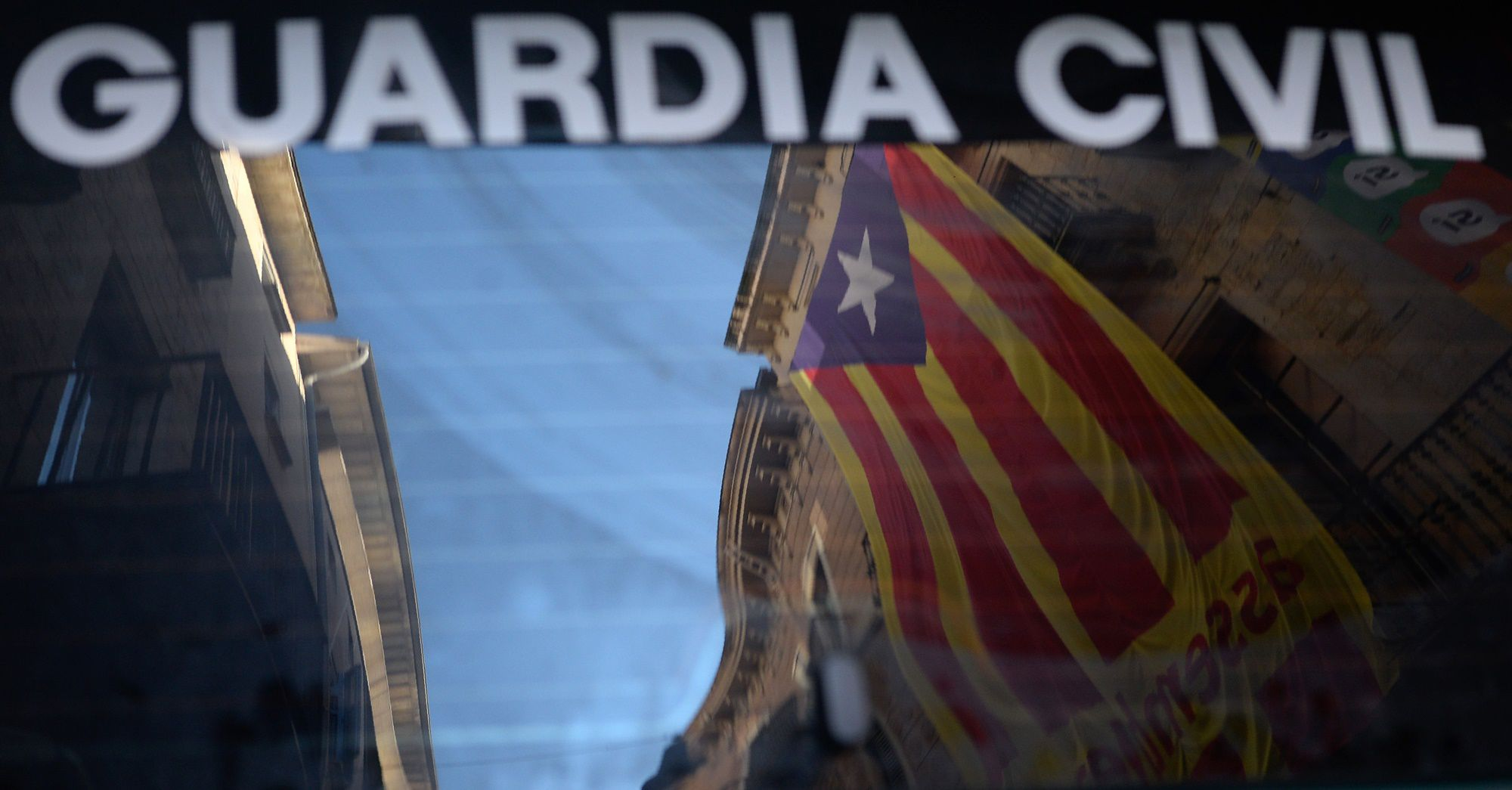 A 'Estelada' (Catalan pro-independence flag) is reflected on the window of a Spanish Civil Guard car in front of the headquarters of the company of waters of Girona on September 19, 2017. The Spanish Guardia Civil registered the company of waters of Girona for alledged misappropriation of funds, when Catalan President Carles Puigdemont was mayor of Girona.  / AFP PHOTO / Josep LAGO        (Photo credit should read JOSEP LAGO/AFP/Getty Images)