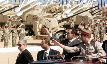 Egyptian President Hosni Mubarak (2R) reviews Egyptian soldiers during a military parade outside Cairo 06 October to mark the 25th anniversary of the Israeli-Arab 1973 October war. The military show is the first since the assassination of Egyptian President Anwar Sadat in 1981.         (Photo credit should read AMR NABIL/AFP/GettyImages)