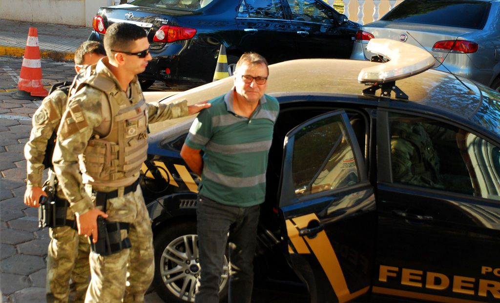 Italian ultra-leftist militant Cesare Battisti arrives escorted by police to the headquarters of the Federal Police in Corumba, Mato Grosso do Sul State, West of Brazil, on October 5, 2017, after a federal judge ordered his preventive detention.  Brazilian police on on the eve detained Battisti, who was convicted of murder in his home country and has been on the run for decades, as he tried to flee to neighboring Bolivia after the Italian government's request for extradition to the Brazilian government. / AFP PHOTO / FABIO MARCHI        (Photo credit should read FABIO MARCHI/AFP/Getty Images)