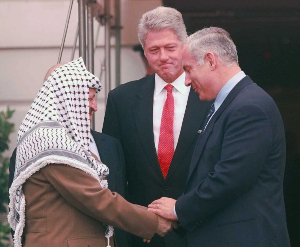 Bill Clinton, Yasser Arafat e Benjamin Netanyahu durante la firma del memorandum di Wye River (Foto: PAUL J. RICHARDS/AFP/Getty Images).
