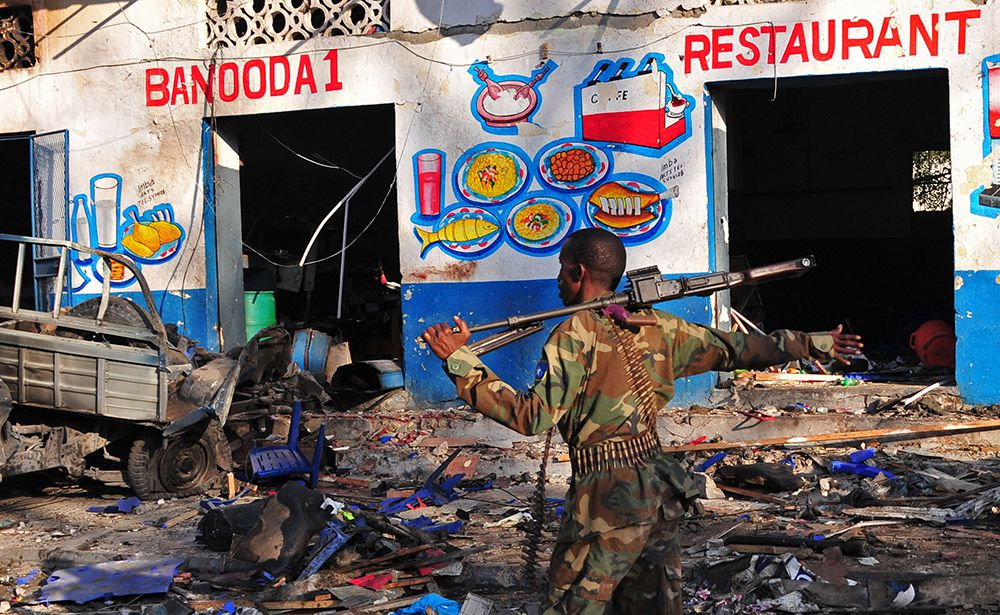 Somali security forces and civilians walk among damages at the scene of a blast on October 29, 2017, a day after two car bombs exploded in Mogadishu. Somalia's security ministry said today that forces had killed two gunmen and captured three after a siege at a Mogadishu hotel following a twin car bombing that left at least 14 dead. The attack began when a car bomb exploded outside the hotel entrance, followed by a minibus loaded with explosives going off at a nearby intersection. / AFP PHOTO / Mohamed ABDIWAHAB        (Photo credit should read MOHAMED ABDIWAHAB/AFP/Getty Images)