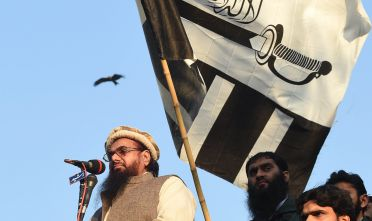 Hafiz Saeed, leader of Jamaat-ud-Dawah (JuD) Pakistan, addresses demonstrators during a protest against the printing of satirical sketches of the Prophet Muhammad by French magazine Charlie Hebdo, in Lahore on January 18, 2015. Anti-Charlie Hebdo protests continued across Pakistan as thousands of people came on streets in almost all major cities chanting slogans against the printing of cartoons of the Prophet Mohammed in the French magazine. AFP PHOTO / Arif ALI        (Photo credit should read Arif Ali/AFP/Getty Images)