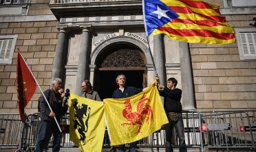 BARCELONA, SPAIN - OCTOBER 30:  A man holds a independence flag outside the Palau Catalan Regional Government Building as Catalonia returns to work following last week's decision by the Catalan parliament to vote to split from Spain on October 30, 2017 in Barcelona, Spain. The Spanish government has responded by imposing direct rule and dissolving the Catalan parliament.  (Photo by Jeff J Mitchell/Getty Images)