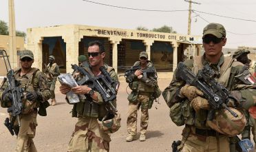 "French soldiers of the 93rd Mountain Artillery Regiment and soldiers of the Malian Armed Forces patrol on June 6, 2015 in Timbuktu, during the joint operation ""La Madine 3"" part of the French Army's ""Operation Barkhane"", an anti-terrorist operation in the Sahel. AFP PHOTO/PHILIPPE DESMAZES        (Photo credit should read PHILIPPE DESMAZES/AFP/Getty Images)"