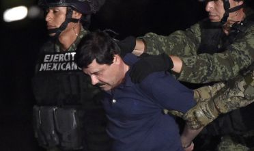 """Drug kingpin Joaquin """"El Chapo"""" Guzman is escorted into a helicopter at Mexico City's airport on January 8, 2016 following his recapture during an intense military operation in Los Mochis, in Sinaloa State. Mexican marines recaptured fugitive drug kingpin Joaquin """"El Chapo"""" Guzman on Friday in the northwest of the country, six months after his spectacular prison break embarrassed authorities.   AFP PHOTO / OMAR TORRES / AFP / OMAR TORRES        (Photo credit should read OMAR TORRES/AFP/Getty Images)"""