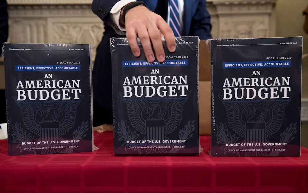 A Congressional staff member delivers copies of US President Donald Trump's Fiscal Year 2019 Government Budget at the House Budget Committee on Capitol Hill in Washington, DC, February 12, 2018. / AFP PHOTO / SAUL LOEB        (Photo credit should read SAUL LOEB/AFP/Getty Images)
