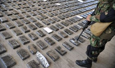 A soldier guards a shipment of 3,9 tons of cocaine seized in a large clandestine laboratory for the production of the drug, during its presentation to the press on March 16, 2013, at the military air base in Tumaco, Narino department, Colombia. Soldiers from special counternarcotics brigade found and destroyed on 13 March, in the municipality of Timbiqui,  Cauca deparment, a huget laboratory to produce cocaine, considered by authorities as the largest collection center for alkaloids processing of the Revolutionary Armed Forces of Colombia (FARC) and from which drug was sent to Central and North America, officials said. AFP PHOTO/Guillermo Legaria        (Photo credit should read GUILLERMO LEGARIA/AFP/Getty Images)