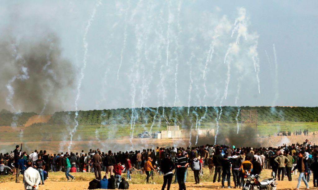 Civili palestinesi cercano riparo dal gas lacrimogeno lanciato contro di essi dalle forze di difesa israeliane nel Giorno della terra. Gaza, 30 marzo 2018. Foto di: MAHMUD HAMS/AFP/Getty Images