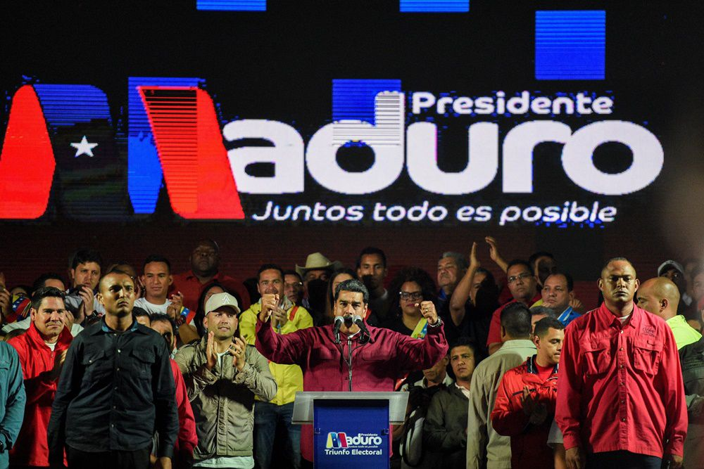Venezuelan President Nicolas Maduro (C) speaks to supporters after the National Electoral Council (CNE) announced the results of the voting on election day in Venezuela, on May 20, 2018 in Caracas. - President Nicolas Maduro was declared winner of Venezuela's election Sunday in a poll rejected as invalid by his rivals, who called for fresh elections to be held later this year. With more than 90 percent of the votes counted,  Maduro had 67.7 percent of the vote, with his main rival Henri Falcon taking 21.2 percent, the National Election Council chief Tibisay Lucena announced. (Photo by Federico PARRA / AFP)        (Photo credit should read FEDERICO PARRA/AFP/Getty Images)