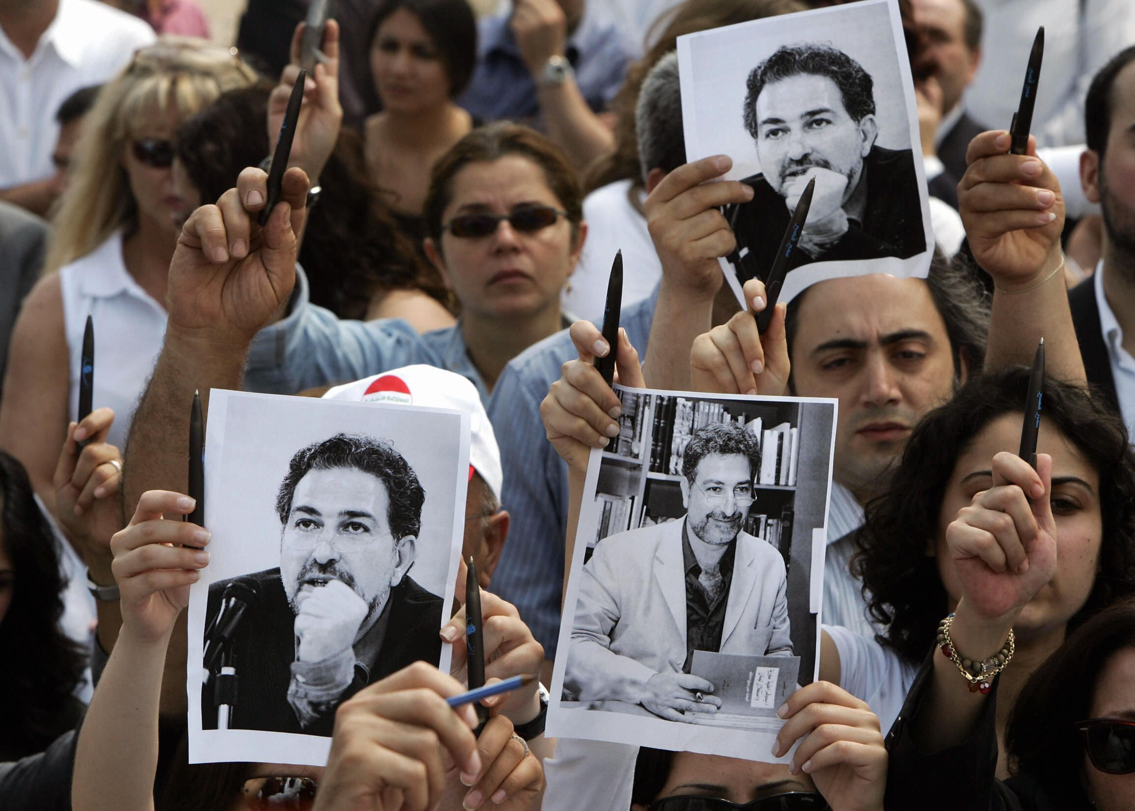 BEIRUT, LEBANON:  Lebanese journalists raise pens and black and white pictures of their assassinated colleague Samir Kassir during a demonstration at Martyrs' square in central Beirut 03 June 2005, to protest his killing in a car bomb explosion the day before. Hundreds of grieving journalists, dressed in black and white, stood in silence around the Statue of the Martyrs in response to a call for the protest by the An Nahar newspaper, where Kassir, 45, was a prominent editorial writer.  AFP PHOTO/RAMZI HAIDAR  (Photo credit should read RAMZI HAIDAR/AFP/Getty Images)