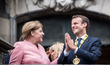 AACHEN, GERMANY - MAY 10: German Chancellor Angela Merkel (L-R) and French President Emmanuel Macron gesture on the balcony of the town hall of Aachen after Macron recieved the International Charlemagne Prize at a ceremony on May 10, 2018 in Aachen, Germany. The award, bestowed annually since 1950, is given to honor leaders who have furthered European unity. (Photo by Lukas Schulze/Getty Images,)