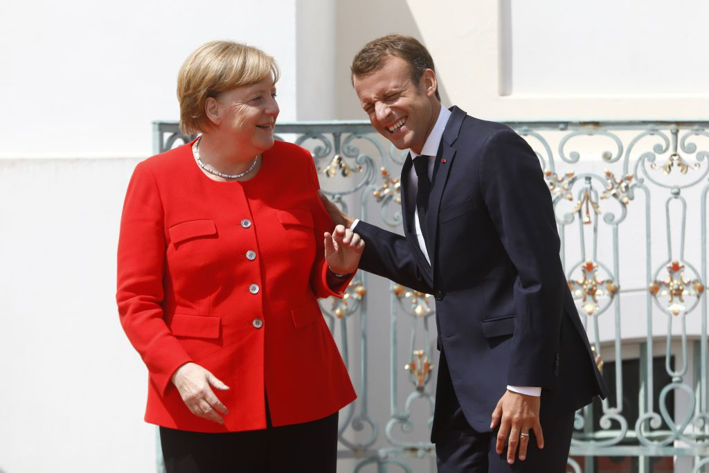 GRANSEE, GERMANY - JUNE 19: German Chancellor Angela Merkel greets French President Emmanuel Macron at Schloss Meseberg governmental palace during German-French government consultations on June 19, 2018 near Gransee, Germany. Merkel, Macron and a selection of their government ministers are coming together today for a day of talks. (Photo by Michele Tantussi/Getty Images)