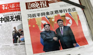 The front pages of Chinese evening newspapers, showing images of China's President Xi Jinping with North Korean leader Kim Jong Un, are displayed at a newspaper stand in Beijing on March 28, 2018.  North Korean leader Kim Jong Un was given a lavish welcome by Chinese President Xi Jinping during a secretive trip to Beijing as both sides seek to repair frayed ties before Pyongyang's landmark summits with Seoul and Washington.  / AFP PHOTO / Fred DUFOUR        (Photo credit should read FRED DUFOUR/AFP/Getty Images)