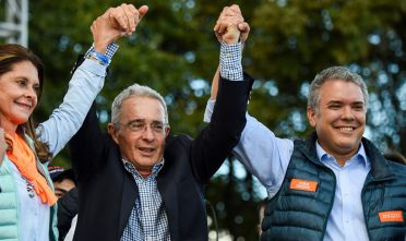 Colombia's presidential candidate for the Democratic Center Party Ivan Duque (L) and Colombian former president Alvaro Uribe (C), take part in the campaign closing rally in Bogota, Colombia on May 20, 2018, ahead of the May 27 presidential election. (Photo by Raul ARBOLEDA / AFP)        (Photo credit should read RAUL ARBOLEDA/AFP/Getty Images)