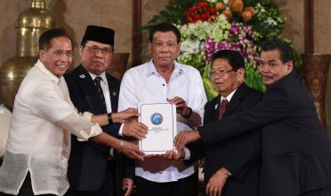 "Philippine President Rodrigo Duterte (C) poses with Secretary of the Peace Process Jesus Dureza (L), Al-Hajj Murad (2nd L), chairman of Moro Islamic Liberation Front (MILF), Ghazali Jaafar (2nd R), vice chairman of MILF and Mohagher Iqbal (R), MILF chief negotiator, as they join hands holding a draft of the Bangsamoro Basic Law (BBL) during a ceremony at the Malacanang Palace in Manila on July 17, 2017. Duterte offered ""genuine autonomy"" to the Philippines' Muslim minority on July 17 to help him defeat Islamist militants who seized a southern city in the gravest challenge to his year-old rule. / AFP PHOTO / TED ALJIBE        (Photo credit should read TED ALJIBE/AFP/Getty Images)"