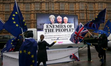 "Pro-EU anti-Brexit demonstrators wave EU and Union Flags as a billboard depicting Britain's Prime Minister Theresa May, Britain's Secretary of State for Exiting the European Union (Brexit Minister) David Davis and Britain's Foreign Secretary Boris Johnson for a campaign by the organisation Avaaz calling for Parliament to have a meaningful vote on the terms of Brexit is driven past outside the Houses of Parliament in central London on December 13, 2017 while MPs debate the EU Withdrawl Bill.  British Prime Minister Theresa May was December 13 facing a rebellion from her own MPs over whether parliament will have a ""meaningful vote"" on the final Brexit deal in what would be a damaging defeat. / AFP PHOTO / Daniel LEAL-OLIVAS        (Photo credit should read DANIEL LEAL-OLIVAS/AFP/Getty Images)"