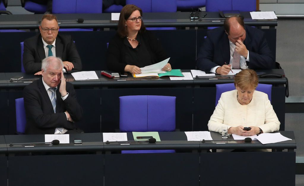 BERLIN, GERMANY - JULY 03:  German Chancellor and leader of the German Chistian Democrats (CDU) Angela Merkel and German Interior Minister and leader of the Bavarian Social Union (CSU) Horst Seehofer attend a session of the Bundestag the day after the two leaders reached a hard-wrung compromise over migration policy on July 3, 2018 in Berlin, Germany. The policy disagreement between the two threatened the decades-old unity of the CDU-CSU fusion. Many analysts see the acrimony generated between the two in the last week as deep and potentially debilitating to the future of Merkel's government.    (Photo by Sean Gallup/Getty Images)