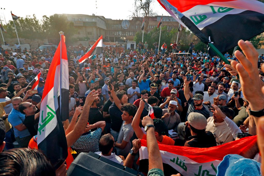 Dozens of Iraqis shout slogans and wave national flags during a demonstration outside the local government headquarters in the southern city of Basra on July 13, 2018 as they protest against poor services, unemployment, and corruption. (Photo by Haidar MOHAMMED ALI / AFP)        (Photo credit should read HAIDAR MOHAMMED ALI/AFP/Getty Images)
