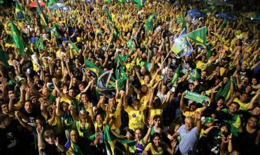 Supporters of far-right presidential candidate Jair Bolsonaro, celebrate in front of the National Congress in Brasilia, after the former army captain won Brazil's presidential election, according to official results that gave him 55.7 percent of the vote, on October 28, 2018. - Far-right former army captain Jair Bolsonaro was elected president of Brazil on Sunday, beating leftist opponent Fernando Haddad in a runoff election after a bitter and polarized campaign. Official results gave the controversial president-elect 55.18 percent of the vote with more than 99.7 percent of the ballots counted. (Photo by Sergio LIMA / AFP)        (Photo credit should read SERGIO LIMA/AFP/Getty Images)