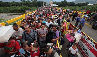 TOPSHOT - Venezuelan citizens cross the Simon Bolivar international bridge from San Antonio del Tachira in Venezuela to Norte de Santander province of Colombia on February 10, 2018. Oil-rich and once one of the wealthiest countries in Latin America, Venezuela now faces economic collapse and widespread popular protest.  / AFP PHOTO / GEORGE CASTELLANOS        (Photo credit should read GEORGE CASTELLANOS/AFP/Getty Images)