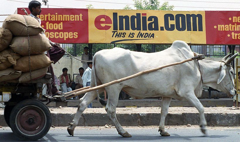 NEW DELHI, INDIA - JUNE 1:  A bullock-driven cart rides past a bus stop billboard advertising one of India's many internet portals 01 June 2000 in New Delhi.  Though parts of the nation remain well below the poverty line, it is estimated that some 500 million USD was invested in dotcom startups in India in 1999.  (Photo credit should read ARKO DATTA/AFP/Getty Images)