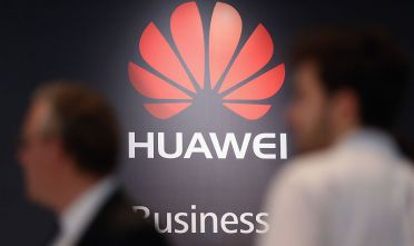 HANOVER, GERMANY - MARCH 16:  Visitors walk past the Huawei stand at the 2015 CeBIT technology trade fair on March 16, 2015 in Hanover, Germany. China is this year's CeBIT partner. CeBIT is the world's largest tech fair and will be open from March 16 through March 20.  (Photo by Sean Gallup/Getty Images)