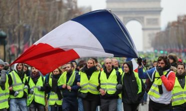"A protester wearing a yellow vest (gilet jaune) waves the French national flag during a demonstration against rising costs of living blamed on high taxes on the Champs-Elysees in Paris, on December 15, 2018. - The ""Yellow Vests"" (Gilets Jaunes) movement in France originally started as a protest about planned fuel hikes but has morphed into a mass protest against President's policies and top-down style of governing. (Photo by Valery HACHE / AFP)        (Photo credit should read VALERY HACHE/AFP/Getty Images)"