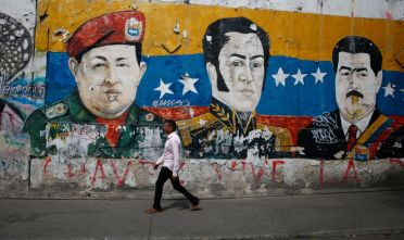 "CARACAS, VENEZUELA - JANUARY 30: A man walks past a mural depicting Venezuela's late President Hugo Chávez, Latin American independence hero Simon Bolivar and Venezuela's President Nicolás Maduro on January 30, 2019 in Caracas, Venezuela. Self-proclaimed ""acting president"" of Juan Guaido Guaido is appealing international leaders and military forces to recognize him as the rightful president and calling on protests against the government of President Nicolás Maduro. (Photo by Marco Bello/Getty Images)"