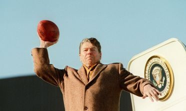 CLEVELAND, :  U.S. President Ronald Reagan throws a football toward the press 11 January 1988 as he boards Air Force One to return to Washington DC. (Photo credit should read JEROME DELAY/AFP/Getty Images)