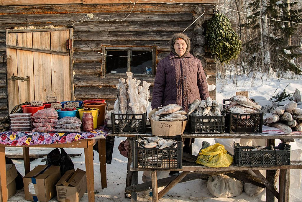 VILLAGE OF YANGUTUM, SIBERIA, RUSSIA - JANUARY, 22: Tuhtabiya poses for a picture near her shack near the Siberian village of Yangutum, on January 22, 2016 in Siberia, Russia.  Local people live in this 'winter' community to sell goods, such as berries, meat and fish, they have caught or gathered, to people driving north to the remote northern areas. They live in these shacks until the winter road becomes impassable. The road, built every winter by pouring water on the surface of the swamps to freeze it, connects the 'main land' area to the remote northern areas across the swamps of Zabolotie. During the warmer seasons, the route through the Zabolotie (about 350 km) is impassable. (Photo by Alexander Aksakov/Getty Images)