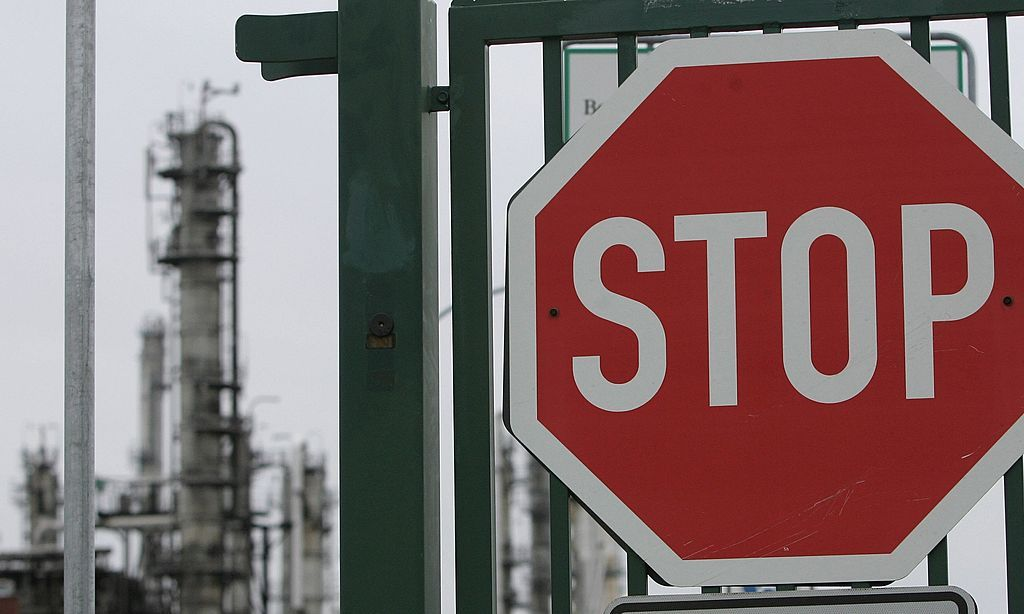 """SCHWEDT, GERMANY - JANUARY 09:  A stop sign stands at an entrance gate to the PCK crude oil refinery January 9, 2007 near the Polish border in Schwedt, Germany. Crude oil from Russia has stopped flowing to the PCK refinery since 6:00 AM January 8 due to a row between Russia and Belarus over how much Belarus should pay for Russian oil. Initial reports claimed Belarus had turned off the flow of crude oil through the """"Druzhba"""" pipeline as a means to negotiate a better price. German oil reserves are still substantial, though Chancellor Angela Merkel announced her country must not depend too much on one source for its energy needs. (Photo by Sean Gallup/Getty Images)"""