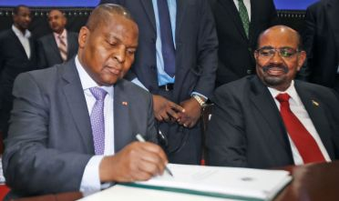 Central African president Faustin-Archange Touadera (L) inks a peace deal next to Sudanese President Omar al-Bashir in Khartoum on February 05, 2019. - The government of the Central African Republic and 14 armed groups on February 05 inked a new peace accord seeking to end years-long fighting that has left thousands of people dead. The accord was initialled by President Touadera for the CAR government and representatives of militias which control most of the chronically-troubled country. (Photo by ASHRAF SHAZLY / AFP)        (Photo credit should read ASHRAF SHAZLY/AFP/Getty Images)