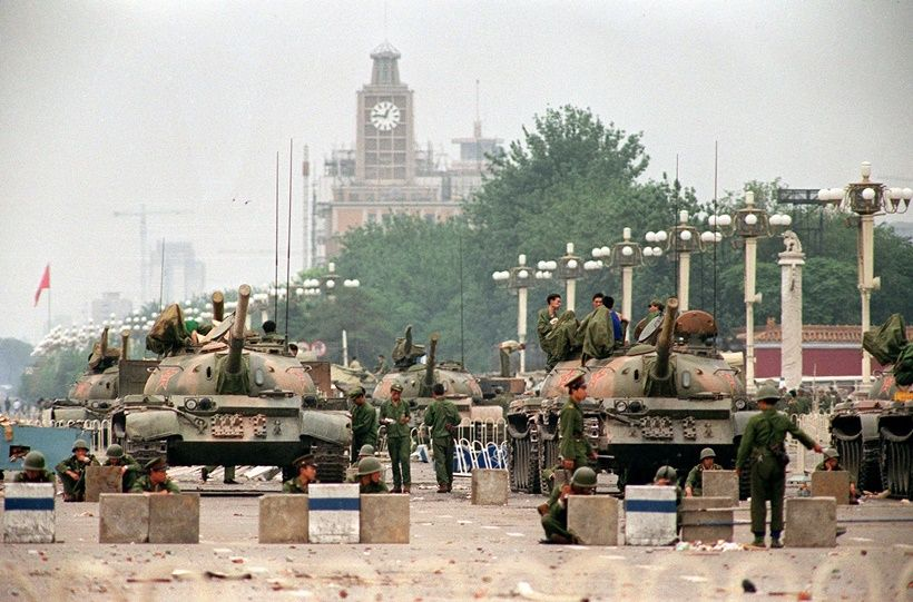 (COMBO) In this combination of pictures created on May 29, 2019, a file photo (top) taken on June 6, 1989 shows People's Liberation Army (PLA) tanks and soldiers guarding Chang'an Avenue leading to Tiananmen Square in Beijing two days after their crackdown on pro-democracy protesters; and a photo (bottom) taken on May 29, 2019 shows traffic on Changan Avenue in front of flags flying at Tiananmen Square in Beijing. - Thirty years after the crackdown on Tiananmen protesters, the tanks that lined Beijing's central avenue have been replaced by countless surveillance cameras perched like hawks on lampposts to keep the population in check. (Photo by Greg Baker and Manny CENETA / AFP)        (Photo credit should read GREG BAKER,MANNY CENETA/AFP/Getty Images)